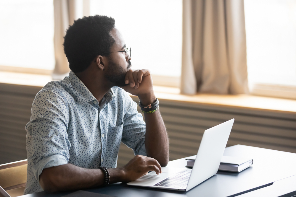 African American man sitting in front of a laptop looking thoughtfully away towards the right